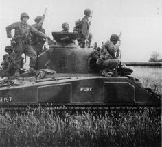 An M4 Sherman, F Co- 2 'FURY' of 66th Armored Regiment with infantry aboard in the Normandy countryside during Operation Cobra. Note particularly the BAR and the soldier with the grenade launcher.