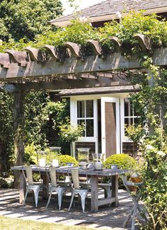 Pergola with vine over dining area. White windows and trim, dark siding, wood pergola, large gray pavers Outdoor Rooms, Outdoor Dining, Outdoor Gardens, Outdoor Decor, Dining Area, Rustic Outdoor, Patio Dining, Rustic Table, Outdoor Tables