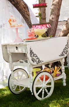 Charming Vintage Wooden Tea Cart Tea anyone? This adorable wooden tea cart speaks for itself! Perfect for a little girl's tea party, where sweet treats are at their reach. Makes for a breathtaking wedding cake display table as well. Ask us about our other tea party accessories. $50.00