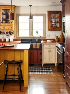"Farmhouse interiors appear as if they were assembled over time. Create that ""unfitted"" look in your kitchen by hanging mismatched vintage cupboards as upper cabinets, choosing cabinets and islands with furniture-like profiles, and opting for assorted cabinet colors. Subtly referencing colonial sculleries, this kitchen handily melds mustard, white, black, red, and brown distressed cabinet finishes."
