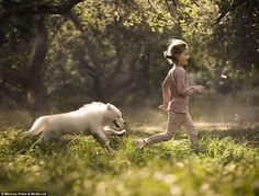 A young girl is chased by her dog as she charges through a woodland - the photographer said ´pets are members of our family´ Ph. Elena Shumilova