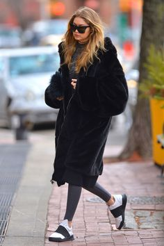 17 March Gigi Hadid was spotted in New York looking relaxed in trainers, sunglasses and an oversize fur coat.   - HarpersBAZAAR.co.uk