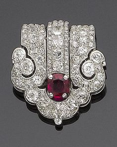 An art deco ruby and diamond clip brooch, by Cartier, circa 1925 The cushion-shaped ruby set within a cushion-shaped, single and rose-cut diamond pierced surround of scrolling design, cushion-shaped and single-cut diamonds approx. 1.80cts total, signed Cartier London, length 2.9cm