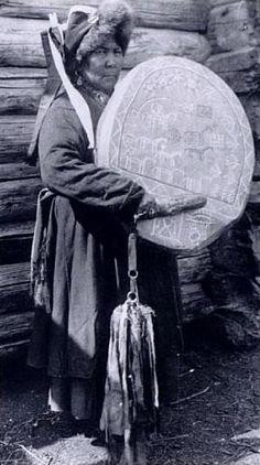 A Teleut Shaman and her Drum, ca. 1930s. The oval drum is divided into the Upper and Lower World. A wavy line separates the worlds. In the Upper World are the Sun, Moon, planets and stars, also horses, riders, birds, and trees. In the Lower World are a man, a fish, and a turtle. These figures, taken together, tell the shaman's story.