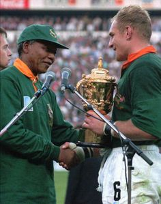 The captain of the South African Rugby Francios Pienaar receives the trophy from President Nelson Mandela, after winning the Rugby World Cup