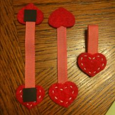 """Bookmarks for school Valentine's.  (Make sure you don't use the really thin magnets, it won't be strong enough to hold on the pages.)   Materials: Felt Embroidery thread Low temp glue gun About 3-1/2"""" of ribbon Magnets (1/2"""" sq. shown)  Cut whatever shape you want. I used hearts for the girls and circles for the boys. Stitch with thread desired pattern. Using low temp glue gun, glue ribbon to felt. Stick on magnets. Voila!"""