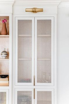 White quatrefoil metal cabinet doors illuminated by brass picture lights beside white built-in cabinets.