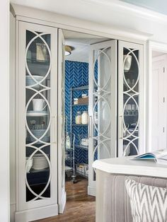 Matthew Quinn Design - Emily Followill - Ivory eclipse mullion built in china cabinets flank a matching double doors opening to a kitchen pantry featuring stainless steel pantry shelves on casters a floor-to-ceiling blue herringbone tile backsplash.