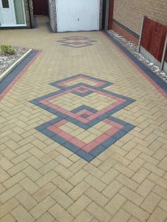 Block driveway with three interlocking diamond shapes in black with red edging.
