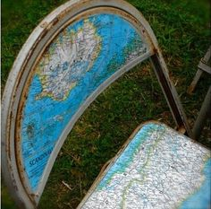 Decoupage maps onto worn out simple metal folding chairs