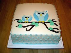 mother and baby owl, made from blue fondant, perched on a brown branch with green leaves, on top of a white, square-shaped cake, owl baby shower cake, with pale blue details