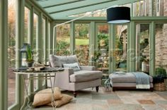 Armchair and footstool in garden conservatory of Sherford barn conversion  Devon  UK
