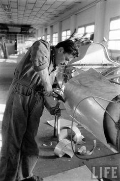 A Ferrari technician is hand-fabricating a body panel for a Lancia/Ferrari D50 headed to the Monaco GP. Maranello,  1956.
