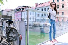 Fashion blogger Veronika Lipar of Brunette From Wall Street wearing light blue jeans, pale pink sneakers, black and white striped top, and white mini bag on weekend in Ljubljana