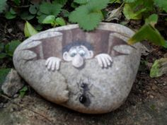 a guy sticking out of  a hole and a realistic ant - painted rock