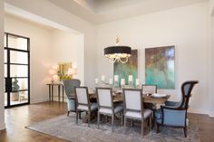 With a bold entrance, the dining room is the first impression for this home.  Presented in front of loud and unique abstract art, the head chairs of the table finish framing the stunning dining room with rounded backs to mirror the rounded chandelier.