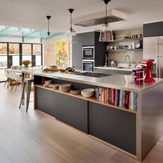 Open-plan kitchen with wood flooring, exposed brick wall and stainless steel island unit