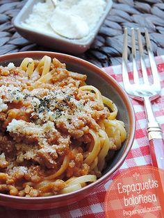 Espaguetis a la boloñesa    500 gr. de espaguetis     1 cebolla     4 zanahorias     2 dientes de ajo     500 gr. de carne picada de ternera     5 tomates grandes o 1 lata de tomates pelados     1 cucharadita de azúcar     1/2 cucharadita de comino en polvo y 1/2 de nuez moscada     1 cucharadita de pimentón y 1 de cilantro en polvo (opcional)     1/2 litro de caldo de ternera     Queso rallado, por ejemplo, parmesano     Sal y pimienta     Aceite