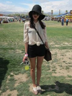 Coachella Festival Style: The perfect mix of femme and goth. Here, this festivalgoer paired black shorts with a sheer blouse, a black floppy hat, and dark red lips.