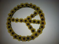 Wooden peace sign, painted black with sunflowers.