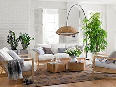 aranżacja salonu z zielonymi kwiatami i drewnianymi meblami na tle ściany z białej cegły