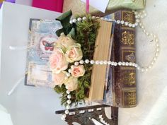 "Easy to make floral arrangement. Vintage tea party bridal shower.    Hollow cardboard book from Michael""s,  moss, spray roses and inexpensive string of pearls"