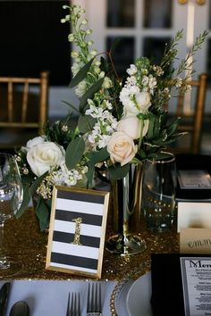 gold and black wedding tablescape with rose floral centerpiece