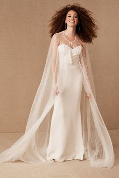 Scattered all over with tiny pearls, this flowing cape effortlessly combines ethereal beauty and understated luxury. Tassel ties at the neckline complete the look.
