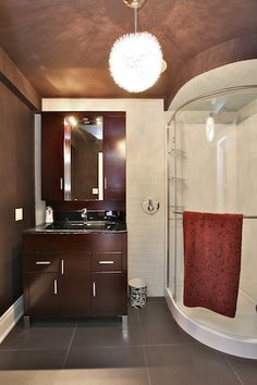 Glamorous Victorian in Yorkville: The guest bathroom has porcelain flooring, glass subway tiles and a funky light fixture
