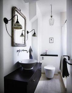 シックなカラーの手洗いカウンターには、アンティーク風のミラーをコーディネート。ミラーの両脇や天井からさがったライトもこだわりのデザインでまとまっています。