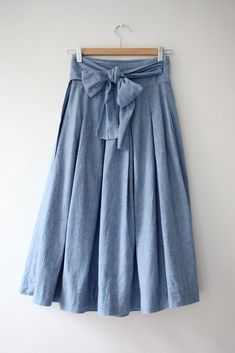 Love the bow. Like jeans but a skirt.