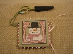 This is a combination scissor fob, needle-book and pin-keep. I cross-stitched the snowman design, then finished with mat board, fabric, felt and ribbon.