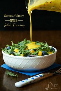 A vertical pour shot of Sweet Spicy Mango Salad Dressing onto an arugula salad