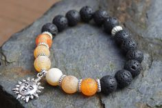 What you see is what you get - this is the only one of this bracelet I will make! Get it before its gone! - Silver tone blazing sunshine charm and accents. - Orange and yellow crackled agate, Dragons Veins beads, 10mm. - Black lava stone beads, 10mm. - Latex-free PowerCord. - 7 Inches un-stretched (approximately). This bracelet best fits people with a medium frame. - Ships from Canada.  The unique, brightly colored Dragons Veins beads and sunshine charm give this bracelet lots of energy…