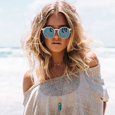 Look praia com óculos escuros e blusa transparente.