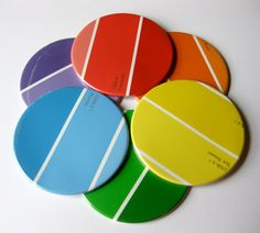 Paint sample coasters. Paper is sandwiched between a sheet of clear plastic(mylar) and a metal base