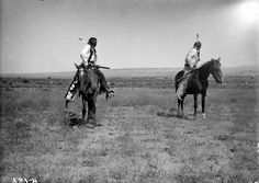 Native American (Ute) scouts pose on horseback; both men look back over their shoulders - Poley - 1899
