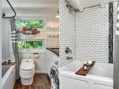 Another example of an efficient tiny house bathroom with a tub as well as a washing machine and dryer. The dark wood floor contrasts very nicely with the white wood walls as well as the subway tile walls surrounding the tub. Modern Tiny House, Tiny House Living, Tiny House Plans, Tiny House Design, Simple Bathroom Designs, Contemporary Bathroom Designs, Alpha Tiny House, Tiny House Appliances, Bathroom Photos