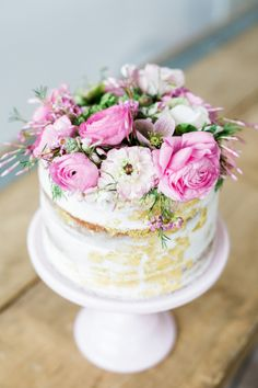 The perfect spring cake with gold accents and gorgeous florals on top.