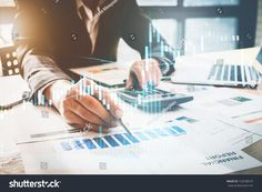 Close up Businessman hand holding pen and pointing at finance paperwork and using calculator for do math on wooden desk at office. business finance concept.
