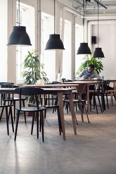 Simple wooden furniture and industrial lighting - Scandi style with an industrial edge at Coffee Collective in Copenhagen, Denmark