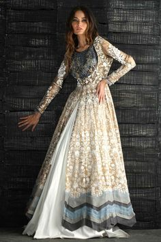 A wonderful combination featuring Gold emboss Anarkali dress, with blue blouse and white Cotton Lehnga for a Perfect Mehndi Dress. Therefore this backless gown is a perfect example of Nida Azwer's Traditional yet Contemporary formal dress.  #nidaazwer #mehndi #henna #mehndidresses #bridal #partydresses #wedding #pakistani