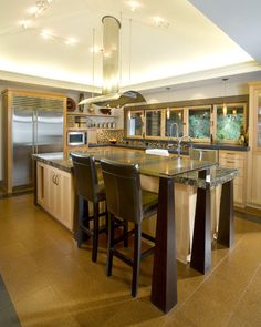 Wanting the range hood in the island bench, but not centred, so it is not a feature.  Like the raised area , but want a whitegood appliances pillar, for a raised oven and dishwasher. Also want a large wooden table in the same area, kitchen, but for dining,eating. Like the kitchen/dining area to be the largest communal room in the house.