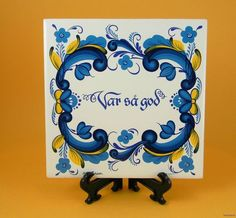 BERGGREN M D Larson VAR SA GOD tile trivet rosemaling blue yellow  var så god means hello if you are answering the phone, it means please if you are asking for something.  literally it means was so good.