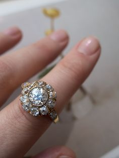 A typical Victorian cluster made in 18k yellow gold featuring a bezel set center stone surrounded by a halo of diamonds in a more elaborate setting then later Deco clusters.