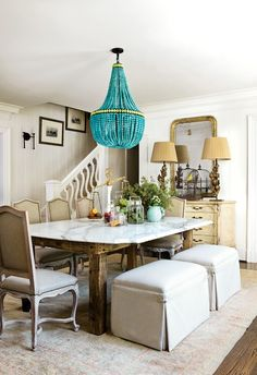 love. this. dining room.  linen ottomans...turquoise chandelier...wood and marble table...gilt mirror