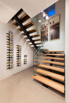 Wine Rack Ideas - Show Off Your Bottles With A Wall Mounted Display | The staggered heights of these three wine racks follow the line of the staircase and create a simple display for all the wine bottles.