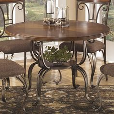 "Plandybird Brown Round Dining Room Furniture Set, Table w/ 4 Chairs  Plandybird Brown Round Dining Room Furniture Set, Table w/ 4 Chairs Rich with flowing traditional beauty, the ""Plandybird"" dining collection takes a warm medium brown wood finish and combines it with dark bronze color powder coat finished welded steel frames that features a scrolling design that flawlessly captures the elegance of traditional style. Search ""Plandybird"" to see the whole collection.  http://www.stor.."
