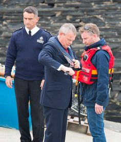 Martin Clunes (Doc Martin) fussing with his life jacket while John Marquez (PC Joe Penhale) looks on during filming of Series 7 in Port Isaac, Cornwall, April 17, 2015. Photo courtesy of Doc Martin's Cornwall