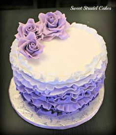 Decorated in fondant ruffles and topped with gumpaste roses.